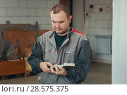Купить «Adult man in uniform working with metal detail at CNC machine at factory with lathes», фото № 28575375, снято 5 июня 2018 г. (c) Константин Шишкин / Фотобанк Лори
