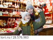 Купить «Young girl and her mother are choosing decorations for Christmas tree», фото № 28576983, снято 19 декабря 2017 г. (c) Яков Филимонов / Фотобанк Лори
