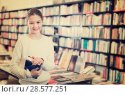 Купить «Portrait of smiling preteen girl holding thick book in bookstore interior», фото № 28577251, снято 22 февраля 2018 г. (c) Яков Филимонов / Фотобанк Лори