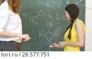 Купить «Pretty smiling young female college student writing on the blackboard during a chemistry class.», фото № 28577751, снято 21 февраля 2019 г. (c) Vasily Alexandrovich Gronskiy / Фотобанк Лори
