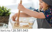 Купить «Cute little girl mixing the dough for cookies with wooden spoon in glass bowl», фото № 28581043, снято 18 июля 2018 г. (c) Константин Шишкин / Фотобанк Лори