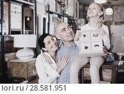 Купить «Family is holding new curbstone that their choosing for bedroom in the furniture store.», фото № 28581951, снято 27 декабря 2017 г. (c) Яков Филимонов / Фотобанк Лори