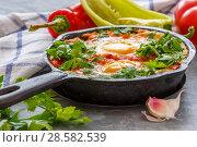 Shakshuka in a cast iron pan. Стоковое фото, фотограф Марина Сапрунова / Фотобанк Лори