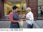 Купить «Москва, продавец из магазина раздаёт подарки гостям на Никольской улице», эксклюзивное фото № 28586031, снято 13 июня 2018 г. (c) Дмитрий Неумоин / Фотобанк Лори