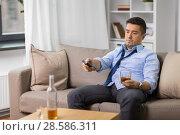 Купить «drunk man with tv remote drinking alcohol at home», фото № 28586311, снято 24 ноября 2017 г. (c) Syda Productions / Фотобанк Лори