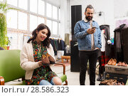 couple choosing footwear at vintage clothing store. Стоковое фото, фотограф Syda Productions / Фотобанк Лори