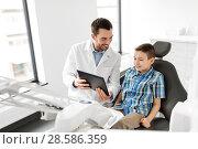Купить «dentist showing tablet pc to kid patient at clinic», фото № 28586359, снято 22 апреля 2018 г. (c) Syda Productions / Фотобанк Лори