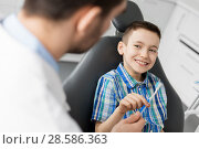 Купить «dentist giving toothbrush to kid patient at clinic», фото № 28586363, снято 22 апреля 2018 г. (c) Syda Productions / Фотобанк Лори