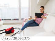 Купить «woman with tablet pc and vacuum cleaner at home», фото № 28586375, снято 29 апреля 2018 г. (c) Syda Productions / Фотобанк Лори