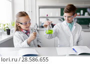 Купить «kids with flask and magnifier at chemistry class», фото № 28586655, снято 19 мая 2018 г. (c) Syda Productions / Фотобанк Лори