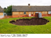 Купить «Sinkhole  in a back garden in Egremont Cumbria as a result of mining subsidence when an old mine shaft opened up, England, UK. June 2005», фото № 28586867, снято 21 июля 2018 г. (c) Nature Picture Library / Фотобанк Лори