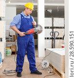 Builder working with handheld disc grinder. Стоковое фото, фотограф Яков Филимонов / Фотобанк Лори