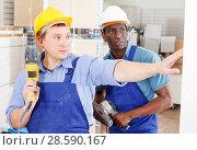 Купить «Builders working with electric tools», фото № 28590167, снято 4 мая 2018 г. (c) Яков Филимонов / Фотобанк Лори