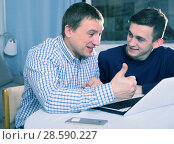 Adult male with his son are resting together and playing on laptop. Стоковое фото, фотограф Яков Филимонов / Фотобанк Лори