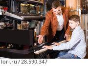 Купить «Seller shows the teen keyboard», фото № 28590347, снято 29 марта 2017 г. (c) Яков Филимонов / Фотобанк Лори