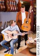Купить «Seller demonstrating acoustic guitar to boy», фото № 28590359, снято 29 марта 2017 г. (c) Яков Филимонов / Фотобанк Лори