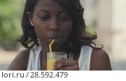 Купить «Portrait of upset young afro woman drinking juice outside in cafe», видеоролик № 28592479, снято 9 августа 2017 г. (c) Vasily Alexandrovich Gronskiy / Фотобанк Лори