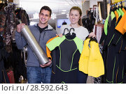Купить «Male and girl standing with diving costumes and oxygen balloon», фото № 28592643, снято 25 января 2018 г. (c) Яков Филимонов / Фотобанк Лори