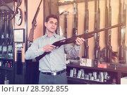 Cheerful male hunter choosing shotgun in store. Стоковое фото, фотограф Яков Филимонов / Фотобанк Лори