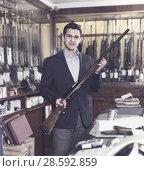 Купить «Salesman in hunting store demonstrating shotgun», фото № 28592859, снято 11 декабря 2017 г. (c) Яков Филимонов / Фотобанк Лори
