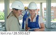 Купить «Construction worker and engineer working on building site, using digital tablet», видеоролик № 28593627, снято 23 июля 2017 г. (c) Vasily Alexandrovich Gronskiy / Фотобанк Лори
