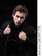 Купить «Resolute man in black jacket waist up shot», фото № 28597775, снято 13 декабря 2019 г. (c) Гурьянов Андрей / Фотобанк Лори