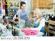 Купить «Two attentive women tailors working with sewing machines», фото № 28599979, снято 28 января 2020 г. (c) Яков Филимонов / Фотобанк Лори