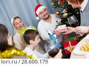 Купить «Smiling man giving Christmas presents to family», фото № 28600179, снято 17 декабря 2017 г. (c) Яков Филимонов / Фотобанк Лори