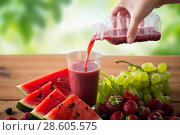 Купить «hand pouring fruit juice from bottle to glass», фото № 28605575, снято 5 августа 2016 г. (c) Syda Productions / Фотобанк Лори