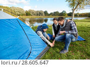 Купить «happy parents and son setting up tent at campsite», фото № 28605647, снято 27 сентября 2015 г. (c) Syda Productions / Фотобанк Лори