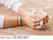 Купить «hands with cacao cup and gay awareness wristband», фото № 28605867, снято 14 ноября 2017 г. (c) Syda Productions / Фотобанк Лори
