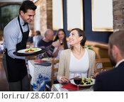 Купить «Waiter male bringing food for man and woman guests», фото № 28607011, снято 11 декабря 2017 г. (c) Яков Филимонов / Фотобанк Лори