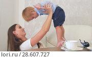 Купить «Happy young mother playing with her baby boy sitting near the tea table», видеоролик № 28607727, снято 7 июня 2017 г. (c) Vasily Alexandrovich Gronskiy / Фотобанк Лори