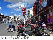 Купить «Тибет, виды города Лхаса. Много мотоциклов и мопедов припарковано на одной из центральных улиц летним днем», фото № 28615459, снято 2 июня 2018 г. (c) Овчинникова Ирина / Фотобанк Лори