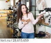 Купить «Young woman in a shoe store», фото № 28615659, снято 22 июня 2018 г. (c) Яков Филимонов / Фотобанк Лори