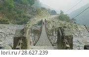 Купить «Two backpackers go along a suspended metal bridge in Nepal», видеоролик № 28627239, снято 17 июня 2018 г. (c) Dzmitry Astapkovich / Фотобанк Лори