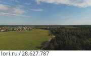 Купить «Aerial view of wheat fields, meadow, forest and village in rural Russia», видеоролик № 28627787, снято 11 июня 2018 г. (c) Андрей Радченко / Фотобанк Лори