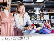 Купить «Portrait of woman designer who is thinking about new dress near mannequin», фото № 28628159, снято 5 мая 2018 г. (c) Яков Филимонов / Фотобанк Лори