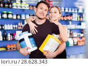 Купить «Loving athletic couple holding plastic jars of sport food supplements in shop interior», фото № 28628343, снято 12 апреля 2018 г. (c) Яков Филимонов / Фотобанк Лори