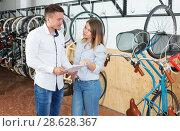 Купить «Man with woman talking about bicycles with characteristic», фото № 28628367, снято 14 мая 2018 г. (c) Яков Филимонов / Фотобанк Лори