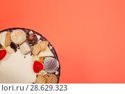 Купить «Фрагмент большого праздничного торта на оранжевом фоне, вид сверху», фото № 28629323, снято 21 июня 2018 г. (c) V.Ivantsov / Фотобанк Лори