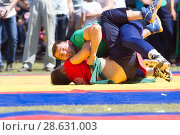 Купить «KAZAN, RUSSIA - JUNE 23, 2018: Traditional Tatar festival Sabantuy - Two male wrestlers fighting on tatami in folk kuresh battle», фото № 28631003, снято 23 июня 2018 г. (c) Константин Шишкин / Фотобанк Лори