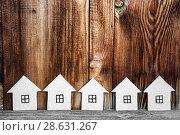 Купить «Несколько картонных домиков на деревянном фоне. Деревянное малоэтажное строительство», фото № 28631267, снято 25 июня 2018 г. (c) Наталья Осипова / Фотобанк Лори