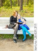 Купить «Embracing mother and daughter read interesting book in a park», фото № 28631311, снято 21 мая 2017 г. (c) Сергей Дубров / Фотобанк Лори