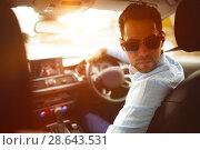 Купить «Man looking back while driving car», фото № 28643531, снято 25 марта 2019 г. (c) Wavebreak Media / Фотобанк Лори