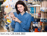 Купить «young girl deciding on brush for decorating house in paint store», фото № 28644383, снято 9 марта 2017 г. (c) Яков Филимонов / Фотобанк Лори