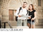 Купить «Attractive man and woman traveling with map and baggage», фото № 28644451, снято 25 мая 2017 г. (c) Яков Филимонов / Фотобанк Лори
