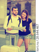Купить «Portrait of young couple with map and baggage», фото № 28644467, снято 25 мая 2017 г. (c) Яков Филимонов / Фотобанк Лори