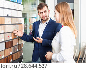 Купить «Competent seller in showroom helping young female client to choose furniture materials for her apartment», фото № 28644527, снято 9 апреля 2018 г. (c) Яков Филимонов / Фотобанк Лори