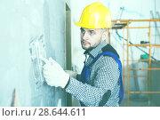 Professional in the helmet is plastering the wall. Стоковое фото, фотограф Яков Филимонов / Фотобанк Лори